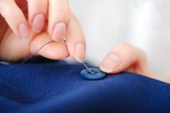 关闭缝合按钮的裁缝手指在车间 免版税图库摄影