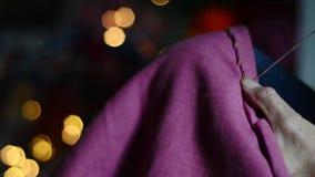 关闭缝暗淡的桃红色织品有舒适,发光的背景的手 影视素材