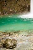 关闭美丽的古铜色岩石在纯净的透明的绿色水中 图库摄影