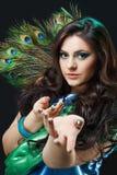 关闭美丽的女孩秀丽画象有孔雀羽毛的,诱剂,召唤手 创造性的构成孔雀 免版税库存图片