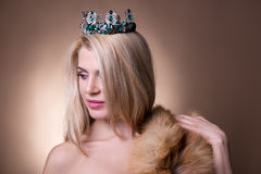 关闭美丽的女孩画象有冠和毛皮的在beig 免版税库存照片