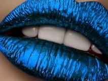 关闭美丽的妇女嘴唇看法有蓝色金属lipstic的 图库摄影