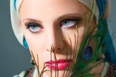 关闭美丽的妇女画象有孔雀羽毛的 库存照片