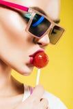 关闭美丽的妇女画象有红色棒棒糖的 免版税图库摄影