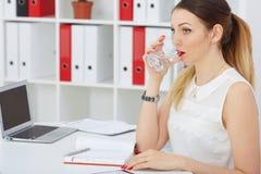 关闭美丽的少妇饮用水的画象在工作地点 库存图片