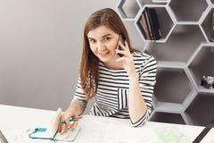 关闭美丽的快乐的年轻女性自由职业者的建筑师画象在桌上在办公室,谈话坐电话 库存图片
