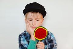 关闭美丽的矮小的男孩画象拿着巨大的棒棒糖在一只手上和看它与严肃的盖帽和衬衣的 免版税库存图片