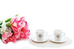 关闭美丽的红色郁金香在花瓶和两个杯子中在白色背景 Copyspace 免版税库存照片