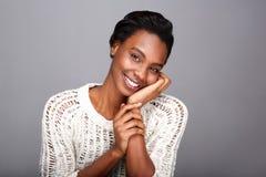 关闭美丽的非裔美国人的妇女在手边微笑的和倾斜的面孔 免版税图库摄影