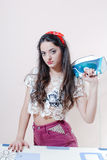 关闭美丽的年轻深色的妇女女孩画象有红色丝带的在她的拿着蓝色铁的头 免版税库存图片