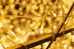 关闭美好的金黄LED温暖的光,圣诞节铜丝串起LED光 Gloden光bokeh被弄脏的摘要 图库摄影