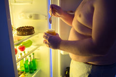 关闭肥胖人断裂饮食在晚上并且吃不健康的甜点 免版税图库摄影