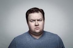 关闭肥胖人画象在怀疑的演播室 免版税库存图片