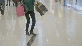 关闭脚跟的滑稽的愉快的妇女运载购物袋走用时尚方式的转动和跳舞在购物中心- 股票视频