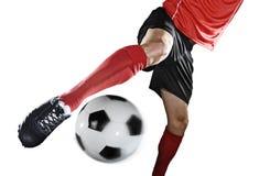 关闭腿和足球运动员足球鞋子踢球的行动的隔绝在白色背景 免版税图库摄影