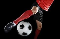 关闭腿和足球运动员足球鞋子踢球的行动的隔绝在黑背景 库存照片