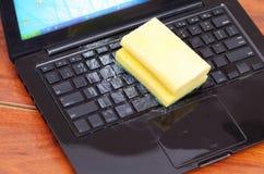 关闭膝上型计算机以水液体下落的损伤弄湿并且溢出在键盘和使用与洗涤剂的一块黄色海绵 免版税库存照片
