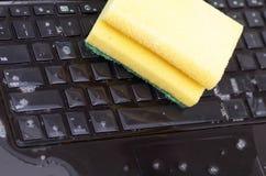 关闭膝上型计算机以水液体下落的损伤弄湿并且溢出在键盘和使用与洗涤剂的一块黄色海绵 库存图片