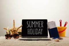 关闭膝上型计算机看法有暑假字法、海星、太阳镜、护照与票和玩具桶的在灰色的沙子 库存照片