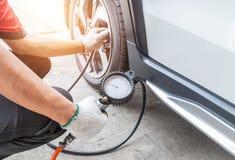 关闭膨胀轮胎和检查气压的技工有表压 库存照片