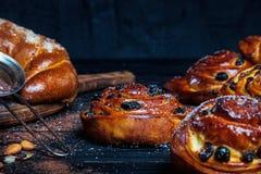 关闭自创小圆面包和新鲜的桂香照片用桂香,杏仁,八角在黑暗的rustik背景 免版税图库摄影