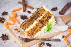 关闭自创胡萝卜糕用葡萄干、核桃和桂香在白色木背景 乳脂干酪结霜 图库摄影
