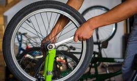 关闭自行车技工在一个车间在轮子的修理过程中有板钳的 库存图片