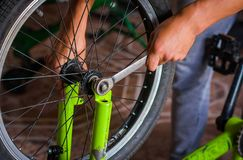 关闭自行车技工在一个车间在轮子的修理过程中有板钳的 免版税库存图片