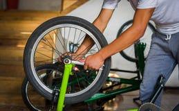 关闭自行车技工在一个车间在轮子的修理过程中有板钳的 免版税库存照片