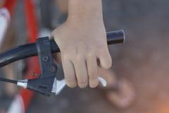 关闭自行车车手在自行车把手的` s手 免版税库存照片