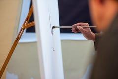 关闭艺术家有刷子绘画图片的妇女的手在艺术演播室日落艺术家演播室创造性图画的帆布 免版税库存图片
