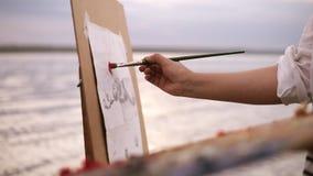 关闭艺术家` s艺术过程 画架和调色板 女孩在帆布上把一些颜色油漆放 被弄脏的湖 股票视频