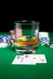 关闭芯片、卡片和威士忌酒玻璃在桌上 免版税库存照片