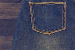 关闭花梢被洗涤的蓝色牛仔裤口袋 在橡木纹理背景,堆行家时尚拷贝空间的被剥去的牛仔裤 库存图片