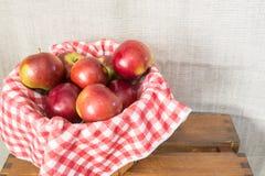 关闭苹果篮子在一块红色和白色方格的布料的 库存图片