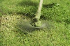 关闭草有草甸领域的灌木清除机 库存图片