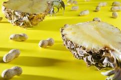 关闭菠萝和花生在壳在五颜六色的背景 与暗影的射击 免版税库存图片