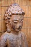 关闭菩萨雕象有竹背景 免版税库存图片