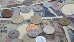 关闭落在钞票的日本硬币日元1000和10000日元背景 股票录像