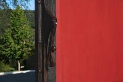 关闭葡萄酒在红色木门的通道门环 门是开放的 免版税库存图片