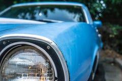 关闭葡萄酒蓝色汽车的老前灯 停放和围拢由树 库存照片