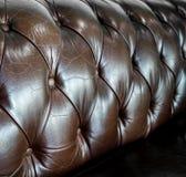 关闭葡萄酒褐色皮革样式的长沙发细节和bac 免版税库存图片