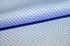 关闭蓝色镶边卷样式衬衣的织品和白色  库存照片