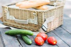 关闭蕃茄和黄瓜在木桌在一个开放野餐篮子前面 库存照片
