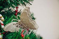 关闭蝴蝶圣诞节玩具在树的 免版税库存图片