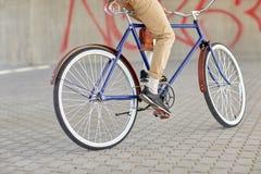 关闭行家人乘坐的固定的齿轮自行车 库存图片