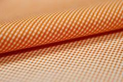 关闭衬衣卷橙色和白色斯科特样式织品  免版税库存图片