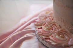 关闭被冰的桃红色花和珍珠装饰在一块婚宴喜饼与丝绸布料 免版税图库摄影