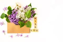 关闭被打开的工艺纸信封充满放置在白色背景的春天开花紫色淡紫色花 顶层 库存照片