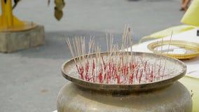 关闭被放入有沙子的罐的香火棍子在佛教寺庙附近户外 影视素材